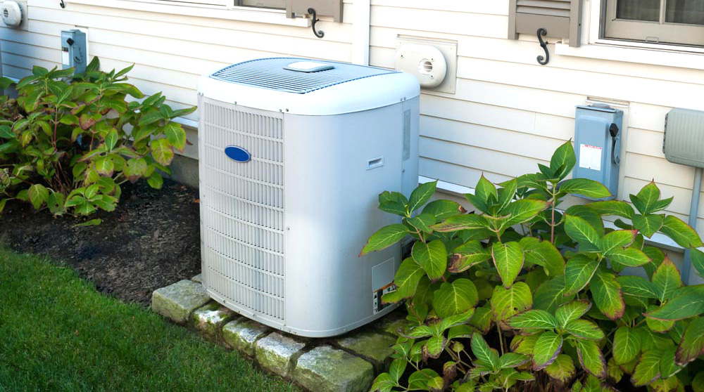 Air conditioning unit sitting on some patio stones in a well-manicured garden beside a home.