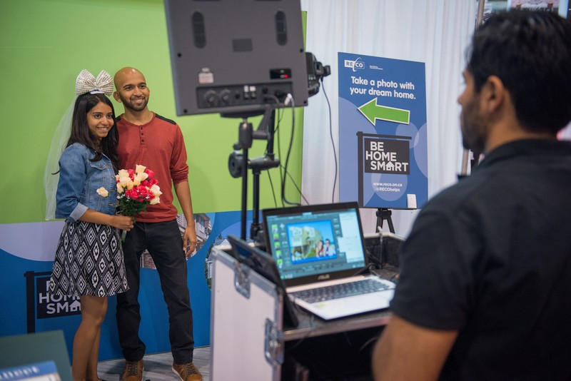 A couple gets their photo taken at the interactive display booth at RECO's booth