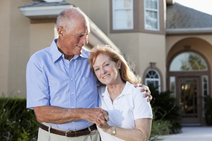 Senior couple in front of home.